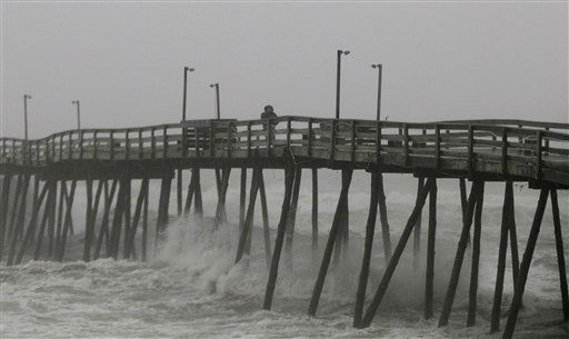 A man walks along Avalon Pier in Kill Devil Hills, Outer Banks, N.C., Saturday, Aug. 27, 2011, as Hurricane Irene reaches the North Carolina coast. Irene slammed into North Carolina&#39;s coast around dawn Saturday with howling winds and drenching rains amid reports of flooding and tens of thousands of people without power. &#40;AP Photo&#47;Charles Dharapak&#41; <span class=meta>(AP Photo&#47; Charles Dharapak)</span>