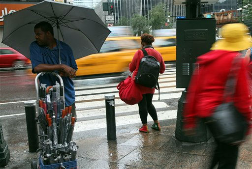 Chikh Lo, of West Africa, left, stands on a street corner in New York selling umbrellas in preparation for Hurricane Irene, Saturday, Aug. 27, 2011, in New York. (AP Photo/Chelsea Matiash)
