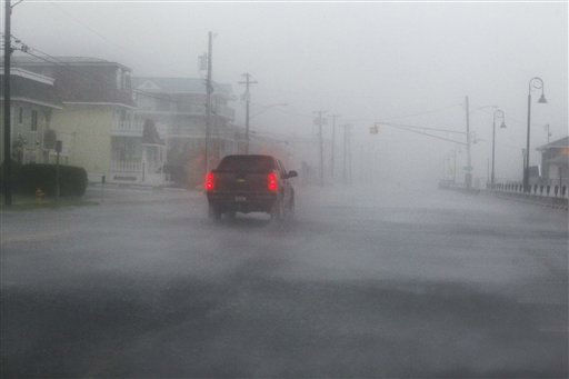 A car drives in a downpour down a deserted street Saturday, Aug. 27, 2011, in Cape May, N.J., as Hurricane Irene arrives. Hurricane-force winds and drenching rains from Irene battered the North Carolina coast early Saturday as the storm began its potentially catastrophic run up the Eastern Seaboard. &#40;AP Photo&#47;Mel Evans&#41; <span class=meta>(AP Photo&#47; Mel Evans)</span>