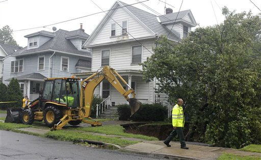 "<div class=""meta image-caption""><div class=""origin-logo origin-image ""><span></span></div><span class=""caption-text"">Workers try to pull out a tree that caved into a sinkhole caused by Hurricane Irene, Sunday, Aug. 28, 2011, Bound Brook, N.J. Flood waters rose all across New Jersey on Sunday, closing roads from side streets to major highways as Hurricane Irene weakened and moved on, leaving 600,000 homes and businesses without power.(AP Photo/Julio Cortez) (AP Photo/ Julio Cortez)</span></div>"