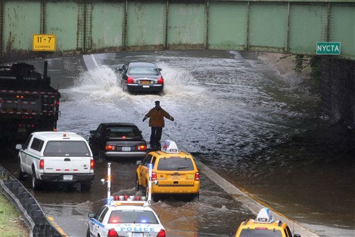 "<div class=""meta image-caption""><div class=""origin-logo origin-image ""><span></span></div><span class=""caption-text"">A police officer slows down traffic due to flooding on a section of the Grand Central Parkway caused by heavy rain from Tropical Storm Irene in Queens, New York, on Sunday, Aug. 28, 2011. Seawater surged into the streets of Manhattan on Sunday as Tropical Storm Irene slammed into New York, downgraded from a hurricane but still unleashing furious wind and rain.  (AP Photo/Gregory Payan) (AP Photo/ Gregory Payan)</span></div>"