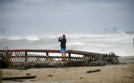 Mike Delaney of Brant Beach takes photos as the waves from Hurricane Irene roll onto the south end of Long Beach Island, Sunday Aug. 28, 2011 in Holgate, N.J.  The casino hotels in Atlantic City can be seen in the background.  &#40;AP Photo&#47;Joe Epstein&#41; <span class=meta>(AP Photo&#47; Joe Epstein)</span>