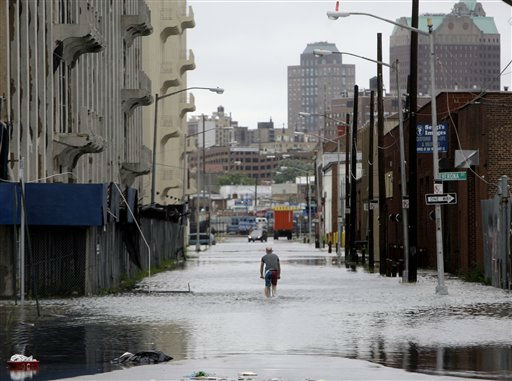 A man pedals through a flooded street in  the Red Hook section of Brooklyn, New York, Sunday, Aug. 28, 2011. Seawater surged into the streets of Manhattan on Sunday as Tropical Storm Irene slammed into New York, downgraded from a hurricane but still unleashing furious wind and rain. The flooding threatened Wall Street and the heart of the global financial network.  &#40;AP Photo&#47;Seth Wenig&#41; <span class=meta>(AP Photo&#47; Seth Wenig)</span>