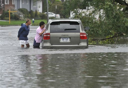 Sam Weintraub helps Joseph Cheung as Cheung&#39;s car got stuck on a flooded street after Tropical Storm Irene swept through Long Island on Sunday, Aug. 28, 2011, in Island Park, N.Y. Irene weakened to winds of 60 mph, well below the 74 mph dividing line between a hurricane and tropical storm. The system was still massive and powerful, forming a figure six that covered the Northeast. It was moving twice as fast as the day before.&#40;AP Photo&#47;Kathy Kmonicek&#41; <span class=meta>(AP Photo&#47; Kathy Kmonicek)</span>
