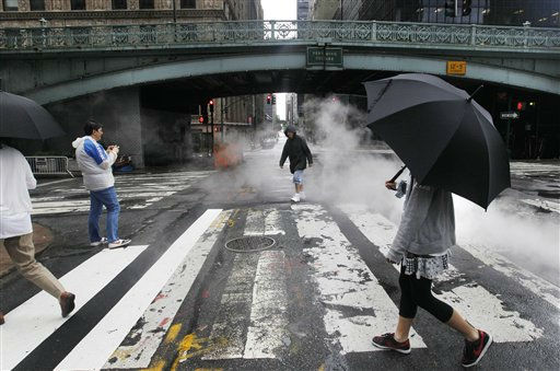 "<div class=""meta image-caption""><div class=""origin-logo origin-image ""><span></span></div><span class=""caption-text"">Italian tourists take pictures in the street around Pershing Square in New York City as the tail end of Tropical Storm Irene passes through the city, Sunday, Aug. 28, 2011. Tropical Storm Irene unleashed furious wind and rain on New York on Sunday and sent seawater surging into the Manhattan streets. But the city appeared to escape the worst fears of urban disaster _ vast power outages, hurricane-shattered skyscraper windows and severe flooding. (AP Photo/Elise Amendola) (AP Photo/ Elise Amendola)</span></div>"