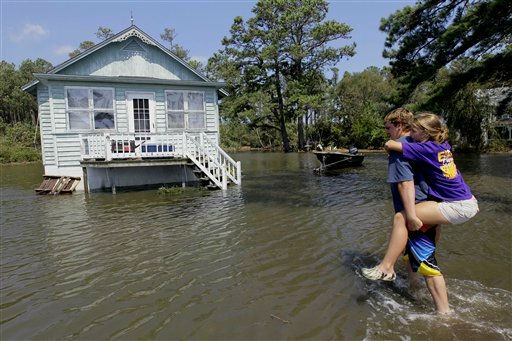 "<div class=""meta image-caption""><div class=""origin-logo origin-image ""><span></span></div><span class=""caption-text"">Residents of Stumpy Point, N.C. make their way into their flooded home following the effects of Hurricane Irene Sunday, Aug. 28, 2011.  Flood waters rose all across New Jersey on Sunday, closing roads from side streets to major highways as Hurricane Irene weakened and moved on, leaving 600,000 homes and businesses without power. (AP Photo/Gerry Broome) (AP Photo/ Gerry Broome)</span></div>"