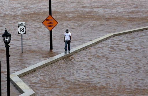 A man walks on top of a wall next  to a flooded highway in New Brunswick, N.J.,  Aug. 28, 2011, as heavy rains left by Hurricane Irene are causing inland flooding of rivers and streams.  Flood waters rose all across New Jersey on Sunday, closing roads from side streets to major highways as Hurricane Irene weakened and moved on, leaving 600,000 homes and businesses without power. &#40;AP Photo&#47;Mel Evans&#41; <span class=meta>(AP Photo&#47; Mel Evans)</span>