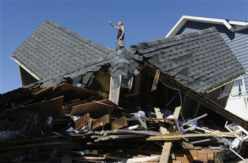 Tom Chase waves atop of his friend&#39;s beach home in the aftermath of Tropical Storm Irene, in East Haven, Conn., Monday, Aug. 29, 2011.  &#40;AP Photo&#47;Jessica Hill&#41; <span class=meta>(AP Photo&#47; Jessica Hill)</span>