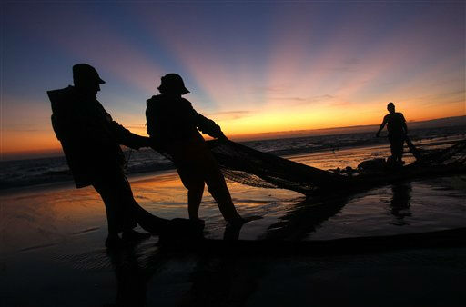 Portuguese fishermen, seen in silhouette, pull their net out of the sea onto the beach Monday, Aug. 29, 2011 in Caparica coast, near Lisbon. Along side the coast, fishermen use the common technique of trawling near the shore and pulling the nets out of the sea onto the beach by using an agricultural tractor. &#40;AP Photo&#47;Francisco Seco&#41; <span class=meta>(AP Photo&#47; Francisco Seco)</span>