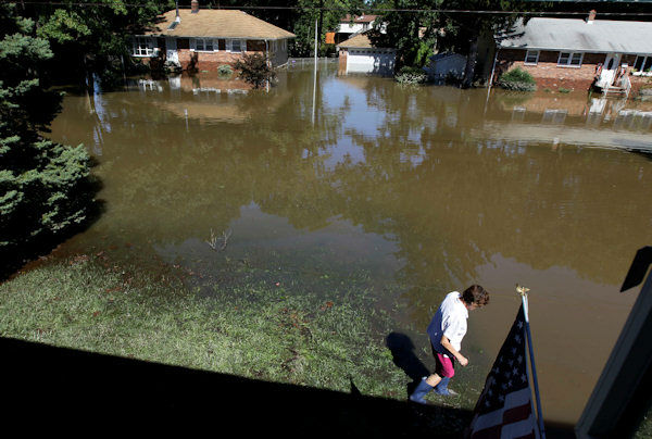 "<div class=""meta ""><span class=""caption-text "">Chris Arnowitz, 65, walks into floodwaters near the front yard of her house in Pompton Lakes, N.J., the morning after the Ramapo River crested following Hurricane Irene, Monday, Aug. 29, 2011. Pompton Lakes is surrounded by three rivers and was seeing serious flooding Monday. Record crests were expected in the area. (AP Photo/Julio Cortez)</span></div>"
