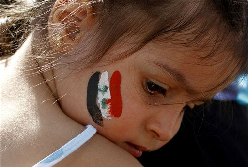 A child with the Syrian flag  painted  on her face sits on her mothers shoulders, during a protest against the regime of Syrian President Bashir Assad in Athens, following prayers marking the end of the holy month of Ramadan, Tuesday Aug. 30, 2011. About 300 people marched through the city center to protest against the Syrian regime&#39;s violent suppression of pro-reform protesters. &#40;AP Photo&#47;Kostas Tsironis&#41; <span class=meta>(AP Photo&#47; KOSTAS TSIRONIS)</span>