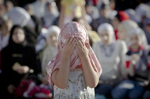 Miri, a 6 year old Muslim girl covers her face, as she  attends Eid al-Fitr prayers in Bucharest, Romania, Tuesday, Aug 30, 2011. More than 2,000 Muslim men and women joined prayers at a stadium in the Romanian capital, in the largest Muslim public gathering to date. Eid al-Fitr marks the end of the holy month of Ramadan, during which Muslims all over the world fast from sunrise to sunset. &#40;AP Photo&#47;Vadim Ghirda&#41; <span class=meta>(AP Photo&#47; Vadim Ghirda)</span>