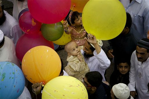 A Pakistani Muslim buys a balloon for his child as he leaves after offering prayers of Eid al Fitr, which marks the end of the Muslim fasting month of Ramadan, in Karachi, Pakistan, Wednesday, Aug. 31, 2011. Eid, one of the most important holidays in the Muslim world, is marked with prayers, family reunions and other festivities. &#40;AP Photo&#47;Fareed Khan&#41; <span class=meta>(AP Photo&#47; Fareed Khan)</span>