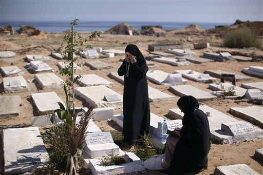Jeria Birn Ismail, left, prays in front of the grave of rebel fighters who were killed in Tripoli fighting against Moammar Gadhafi&#39;s troops, at a cemetery on the first day of Eid al-Fitr in Tripoli, Libya, Wednesday, Aug. 31, 2011. Muslims are celebrating the festival of Eid al-Fitr which marks the end of the holy fasting month of Ramadan. &#40;AP Photo&#47;Alexandre Meneghini&#41; <span class=meta>(AP Photo&#47; Alexandre Meneghini)</span>