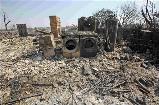 "<div class=""meta ""><span class=""caption-text "">Charred appliances and a fireplace are all that remain of a home in Possum Kingdom Lake, Texas, Wednesday, Aug. 31, 2011, the day after a wildfire swept through the area. Some streets were virtually untouched by the fire on Tuesday, with homes fronted by lawns that could double as putting greens, but others were reduced to rows of scorched stone fireplaces and twisted metal frames. (AP Photo/LM Otero) (AP Photo/ LM Otero)</span></div>"