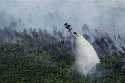 A Louisiana National Guard helicopter dumps water on a burning marsh fire in Eastern New Orleans, Wednesday, Aug. 31, 2011.   Haze from the fire was reported as far west as the Baton Rouge metro area, the National Weather Service said. It expanded its smoke alert from New Orleans and six suburban parishes to 23 parishes, including towns 100 miles from New Orleans. &#40;AP Photo&#47;Gerald Herbert&#41; <span class=meta>(AP Photo&#47; Gerald Herbert)</span>