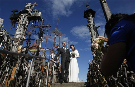 A newlywed couple pose for a picture at the Hill of Crosses, a Lithuanian national pilgrimage site near the city of Siauliai, Lithuania, Saturday, Sept. 3, 2011. Not only crosses but giant crucifixes, carvings of Lithuanian patriots, statues and thousands of tiny effigies and rosaries have been brought by Catholic pilgrims to this site for nearly two centuries. &#40;AP Photo&#47;Petr David Josek&#41; <span class=meta>(AP Photo&#47; Petr David Josek)</span>