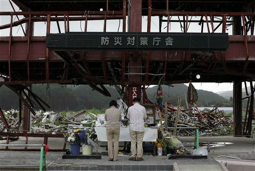 A couple pay respects at a shrine set up at the destroyed disaster prevention center building at Minamisanriku in northeast Japan Sunday, Sept. 4, 2011. Dozens of people took shelter on the roof of the three-story building during the March 11 tsunami, but about 10 survived after the rising waters swept the others off the roof. Japan marks six months since the disaster on Sept. 11. &#40;AP Photo&#47;Greg Baker&#41; <span class=meta>(AP Photo&#47; Greg Baker)</span>