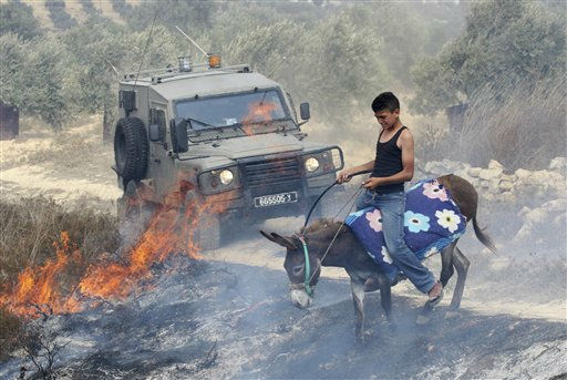 A Palestinian rides his donkey through a burning field as an Israeli army jeep drives by, after arsonists set fire to an olive grove in the West Bank village of Burin, near Nablus, Monday, Sept. 5, 2011. Palestinian witnesses say Jewish settlers set fire to an olive grove in a West Bank village Monday, after a mosque was torched allegedly by Jewish settlers in another West Bank village earlier. Both incidents occurred after the Israeli military razed three buildings in an unauthorized West Bank Jewish settlement outpost before dawn, and clashed with defiant settlers who reject a Supreme Court ruling ordering the enclave to be dismantled. &#40;AP Photo&#47;Nasser Ishtayeh&#41; <span class=meta>(AP Photo&#47; Nasser Ishtayeh)</span>