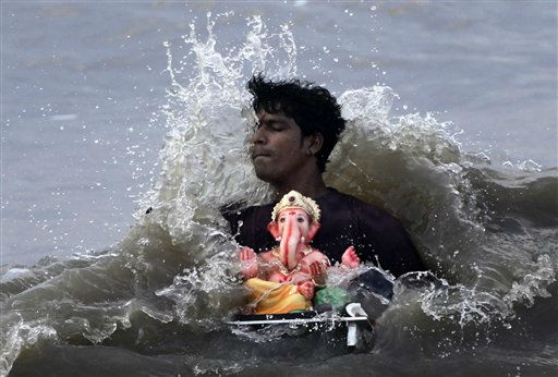 A man carries an idol of Hindu elephant headed god Ganesha for immersing it in the Arabian Sea on the fifth day of the ten day long  Ganesh Chaturti festival in Mumbai, India, Monday, Sept. 5, 2011. The festival celebrates the birth of the Hindu god. &#40;AP Photo&#47;Rajanish Kakade&#41; <span class=meta>(AP Photo&#47; Rajanish Kakade)</span>