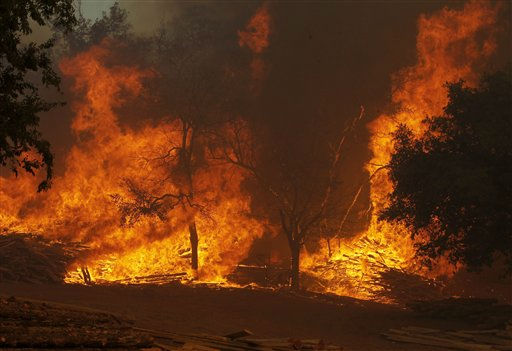 "<div class=""meta ""><span class=""caption-text "">A large wildfire on Highway 71 near Smithville, Texas, Monday, Sep. 5, 2011 burns piles of lumber and ranch posts.  A roaring wildfire raced unchecked Monday through rain-starved farm and ranchland in Texas, destroying nearly 500 homes during a rapid advance fanned in part by howling winds from the remnants of Tropical Storm Lee.  (AP Photo/Erich Schlegel) (AP Photo/ Erich Schlegel)</span></div>"