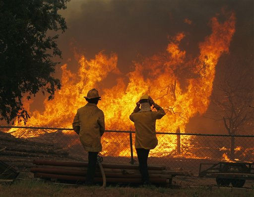 Firefighters from around the state battle a large wildfire on Highway 71 near Smithville, Texas, Monday, Sep. 5, 2011.  A roaring wildfire raced unchecked Monday through rain-starved farm and ranchland in Texas, destroying nearly 500 homes during a rapid advance fanned in part by howling winds from the remnants of Tropical Storm Lee.  &#40;AP Photo&#47;Erich Schlegel&#41; <span class=meta>(AP Photo&#47; Erich Schlegel)</span>