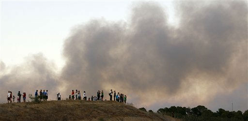 "<div class=""meta ""><span class=""caption-text "">A large plume of smoke rises from a wildfire at onlookers watch from a hill, Monday, Sept. 5, 2011, in Bastrop, Texas.  A roaring wildfire raced unchecked Monday through rain-starved farm and ranchland in Texas, destroying nearly 500 homes during a rapid advance fanned in part by howling winds from the remnants of Tropical Storm Lee. (AP Photo/Eric Gay) (AP Photo/ Eric Gay)</span></div>"