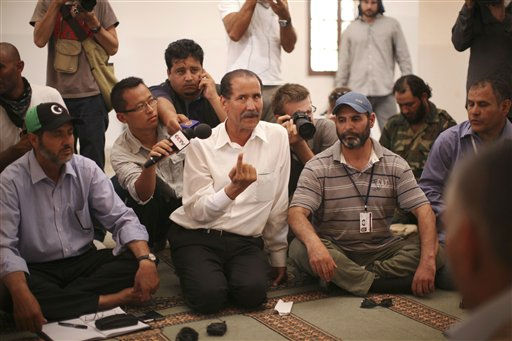 "<div class=""meta ""><span class=""caption-text "">Abdalla Kenshil, chief rebel negotiator, centre, speaks to tribal elders during negotiations in a mosque at a checkpoint between Tarhouna and Bani Walid, Tuesday, Sept. 6, 2011. Moammar Gadhafi is determined to fight his way back to power, the toppled dictator's spokesman said Tuesday, but a large convoy of his soldiers has apparently deserted, crossing the Libyan desert into neighboring Niger.(AP Photo/Alexandre Meneghini) (AP Photo/ Alexandre Meneghini)</span></div>"