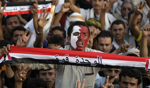 A protestor with Qatari flag painted on his face, holds Yemen&#39;s national flag as he chants slogans during a demonstration demanding the resignation of President Ali Abdullah Saleh, in Sanaa, Yemen, Tuesday, Sept. 6, 2011. Arabic on Yemen&#39;s flag reads, &#34; The Unity is the power&#34;.&#40;AP Photo&#47;Hani Mohammed&#41; <span class=meta>(AP Photo&#47; Hani Mohammed)</span>