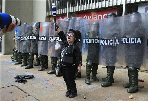A protester gestures in front of riot police officers during a march called by the national teacher&#39;s union to protests against an alleged government plan to change teacher&#39;s health attention in Bogota, Colombia, Wednesday, Sep. 7, 2011. Colombian government denied plans to such changes. &#40;AP Photo&#47;Fernando Vergara&#41; <span class=meta>(AP Photo&#47; Fernando Vergara)</span>