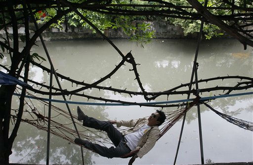 "<div class=""meta ""><span class=""caption-text "">A Thai worker rests under a tree in Bangkok, Thailand Thursday, Sept. 8, 2011. (AP Photo/Sakchai Lalit) (AP Photo/ Sakchai Lalit)</span></div>"