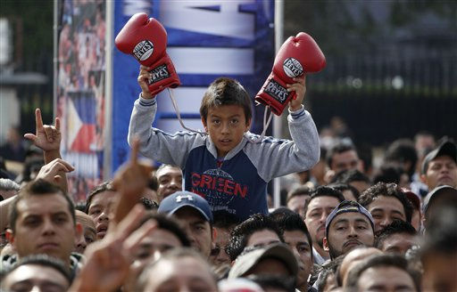 A fan of Mexican boxer Juan Manuel Marquez holds up boxing gloves during a promotion event for his upcoming fight with WBO welterweight boxing champion Manny Pacquiao, of the Philippines, in Mexico City, Thursday Sept. 8, 2011. Pacquiao and Marquez promoted their upcoming Nov. 12 fight to be held at the MGM Grand in Las Vegas. &#40;AP Photo&#47;Eduardo Verdugo&#41; <span class=meta>(AP Photo&#47; Eduardo Verdugo)</span>