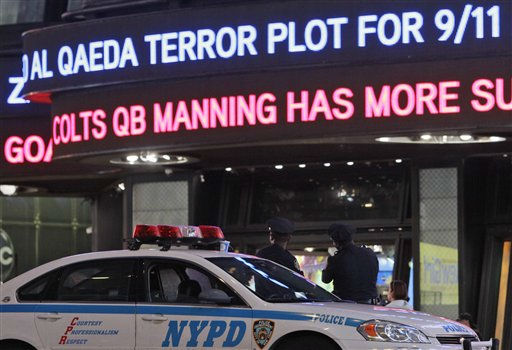 A police officer stands guard in New York&#39;s Times Square as the ABC news ticker displays news of an al-Qaida terror threat, Friday, Sept. 9, 2011. Just days before the 10th anniversary of the Sept. 11 attacks, U.S. counterterrorism officials are chasing a credible but unconfirmed al-Qaida threat to use a car bomb on bridges or tunnels in New York City or Washington. It is the first &#34;active plot&#34; timed to coincide with the somber commemoration of the terror group&#39;s 9&#47;11 attacks a decade ago that killed nearly 3,000 people.  &#40;AP Photo&#47;Mary Altaffer&#41; <span class=meta>(Photo&#47;Mary Altaffer)</span>