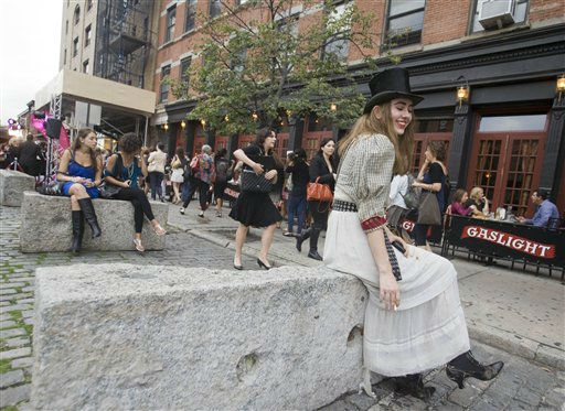A woman dressed in a top-hat sits on a stone bench during the start of Fashion&#39;s Night Out in New York, Thursday, Sept. 8, 2011. &#40;AP Photo&#47;Dan Balilty&#41; <span class=meta>(AP Photo&#47; Dan Balilty)</span>