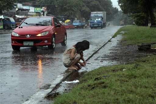 Two girls play at a pool of water in the rain in suburban Quezon city, northern Manila, Philippines, Friday, Sept. 9, 2011. &#40;AP Photo&#47;Pat Roque&#41; <span class=meta>(AP Photo&#47; Pat Roque)</span>
