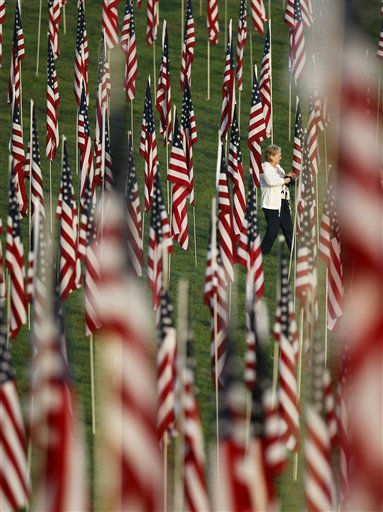 Mary Hauser of Webster Groves, Mo., walks among nearly 3,000 flags set up as part of a remembrance on 10th anniversary of the Sept. 11 terrorist attacks Sunday, Sept. 11, 2011, in St. Louis. &#40;AP Photo&#47;Jeff Roberson&#41; <span class=meta>(AP Photo&#47; Jeff Roberson)</span>