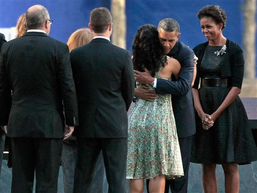 President Barack Obama embraces the family member of a victim of the Sept. 11 terrorist attacks as first lady Michelle Obama, right, stands by at the Sept. 11 Memorial during the 10th anniversary ceremony at the site of the World Trade Center Sunday, Sept. 11, 2011, in New York. &#40;AP Photo&#47;Chip Somodevilla, Pool&#41; <span class=meta>(AP Photo&#47; Chip Somodevilla)</span>