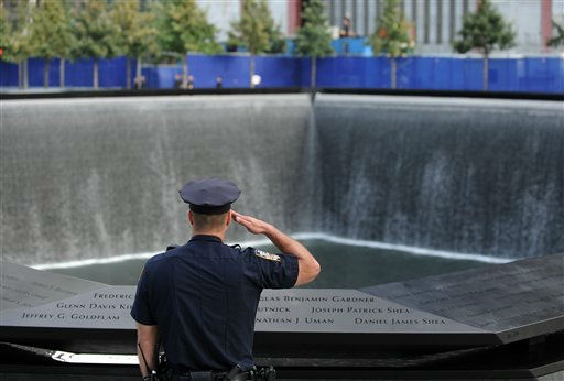 A New York City police officer salutes at the north pool of the Sept. 11 memorial as the national anthem is sung during the 10th anniversary ceremonies at the World Trade Center, Sunday, Sept. 11, 2011, in New York. &#40;AP Photo&#47;Justin Lane, Pool&#41; <span class=meta>(AP Photo&#47; JUSTIN LANE)</span>