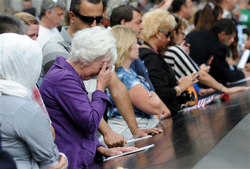 A woman cries over a name inscribed on the edge of the north pool at the National September 11 Memorial in New York during the ceremony marking the 10th anniversary of the attacks on the World Trade Center, Sunday, Sept. 11, 2011. &#40;AP Photo&#47;Justin Lane, Pool&#41; <span class=meta>(AP Photo&#47; Justin Lane)</span>