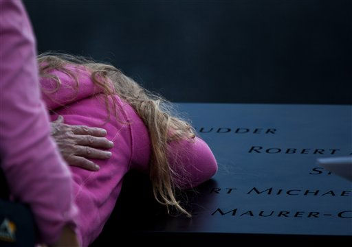 A girl cries over a name inscribed on the edge of the National September 11 Memorial in New York during the ceremony marking the 10th anniversary of the attacks on the World Trade Center, Sunday, Sept. 11, 2011. <span class=meta>(AP Photo)</span>