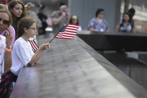 Eliza Peterson holds a flag near the name of her uncle, Norman Rossinow, who was killed Sept. 11, 2001 terrorist attacks, at the Sept. 11 memorial at the World Trade Center site in New York, Sunday, Sept. 11, 2011. &#40;AP Photo&#47;Seth Wenig, Pool&#41; <span class=meta>(AP Photo&#47; Seth Wenig)</span>
