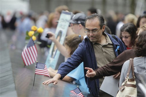 Members of the public run their hands along and make photos of some of the names inscribed on the wall of the Sept. 11 memorial, Sunday, September 11, 2011 in New York. Sunday marked the 10th anniversary of the terrorist attacks on the World Trade Center. &#40;AP Photo&#47;Seth Wenig, Pool&#41; <span class=meta>(AP Photo&#47; Seth Wenig)</span>