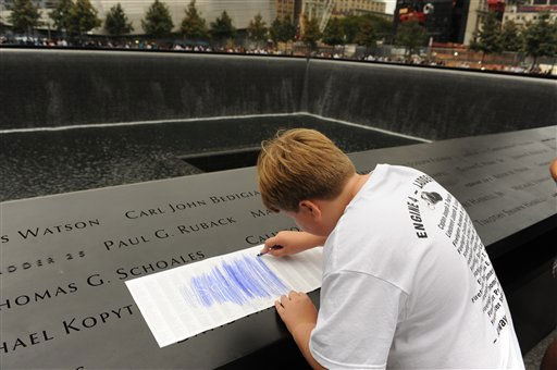 August Larsen, 9, makes an impression of his father, Scott Larsen&#39;s, name from its inscription of the wall at the Sept. 11 memorials? south pool, Sunday, Sept. 11, 2011 in New York. Sunday marked the 10th anniversary of the terrorist attacks on the World Trade Center. &#40;AP Photo&#47;Aaron Showalter, Pool&#41; <span class=meta>(AP Photo&#47; AARON SHOWALTER)</span>
