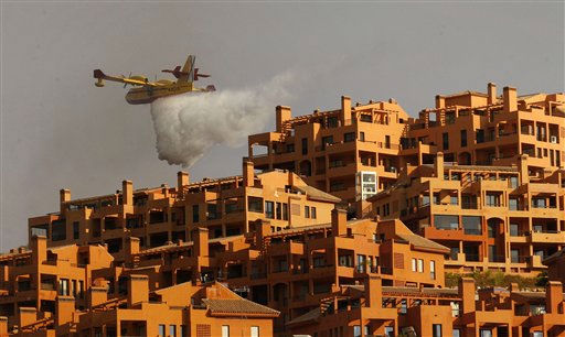 "<div class=""meta ""><span class=""caption-text "">A firefighting plane dumps water near a buildings in Marbella, southern Spain, Monday, Sep. 12, 2011. A forest fire is burning out control after forcing the evacuation of 300 homes in the town of Mijas near the resort city Marbella. (AP Photo/Sergio Torres) (AP Photo/ Sergio Torres)</span></div>"