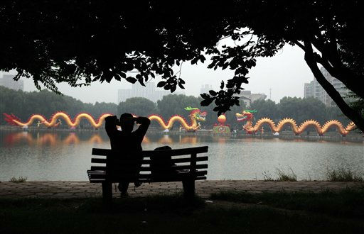 A woman sits back to enjoy the view near a giant dragon shaped lantern set up to mark mid-autumn festival in Beijing, China, Monday, Sept. 12, 2011. &#40;AP Photo&#47;Ng Han Guan&#41; <span class=meta>(AP Photo&#47; Ng Han Guan)</span>