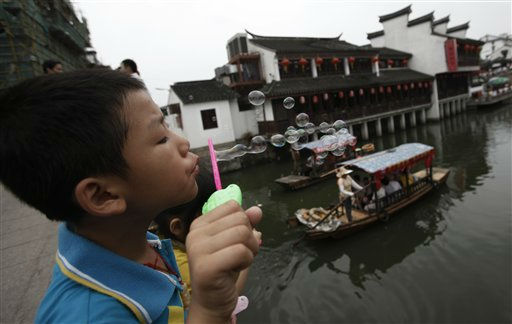 A young visitor blows soap bubbles from a bridge over a canal on the Mid-Autumn Festival holiday, Monday, Sept. 12, 2011 in Shanghai, China. The Mid-Autumn Festival, also known as Moon Festival, falling on the 15th day of the 8th month of the lunar calendar took place on Sept. 12 this year. &#40;AP Photo&#47;Eugene Hoshiko&#41; <span class=meta>(AP Photo&#47; Eugene Hoshiko)</span>