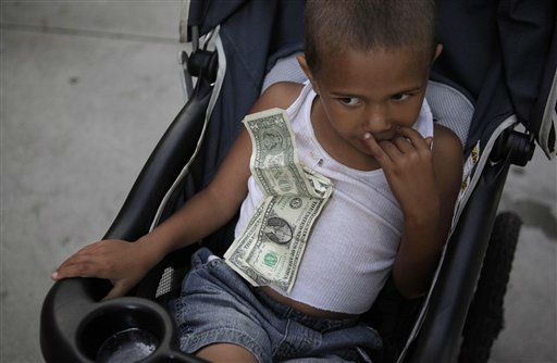 4-year-old Nathan Hobbs, who lives in a homeless shelter with his mother, sits in a stroller with one dollar bills he received  for his birthday pinned to his chest in Los Angeles, Wednesday, Sept. 14, 2011. The ranks of the nation?s poor have swelled to a record 46.2 million ? nearly 1 in 6 Americans ? as the prolonged pain of the recession leaves millions still struggling and out of work.  &#40;AP Photo&#47;Jae C. Hong&#41; <span class=meta>(AP Photo&#47; Jae C. Hong)</span>