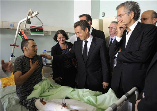 French President Nicolas Sarkozy, center, and Britain&#39;s Prime Minister David Cameron, hidden behind Sarkozy, visit injured people in the Tripoli Medical center, Tripoli Thursday Sept. 15, 2011. British Prime Minister David Cameron and French President Nicolas Sarkozy arrived in Tripoli on Thursday, the first heads of government to visit Libya since revolutionary forces seized the capital, a major endorsement for the North African nation&#39;s new rulers. Cameron and Sarkozy planned to meet with the leaders of the National Transitional Council, the closest thing Libya&#39;s new rulers have to a functioning government, to discuss aid to help the transition to democracy after four decades of authoritarian rule by fugitive leader Moammar Gadhafi. At right is French Foreign Minister Alain Juppe, second right is French philosopher Bernard-Henri Levy. &#40;AP Photo&#47;Eric Feferberg, Pool&#41; <span class=meta>(AP Photo&#47; Eric Feferberg)</span>