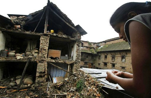Nepalese woman looks out of a window at debris of collapsed buildings damaged by Sunday&#39;s earthquake in Katmandu, Nepal, Monday, Sept. 19, 2011. Rescue workers raced Monday to clear roads blocked by mudslides as they scrambled to reach remote villages cut off after the powerful earthquake shook northeast India, Nepal and Tibet. &#40;AP Photo&#47;Niranjan Shrestha&#41; <span class=meta>(AP Photo&#47; Niranjan Shrestha)</span>