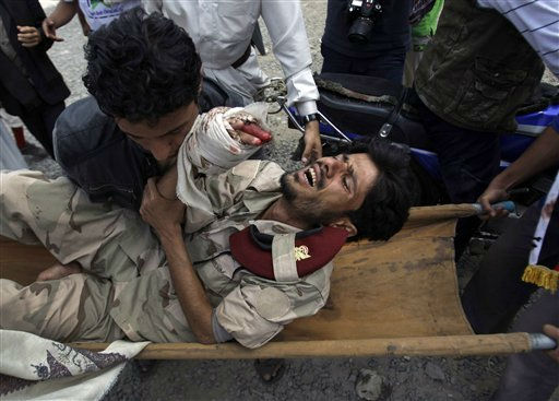 Anti-government protestors carry a wounded defected soldier from the site of clashes with security forces to a field hospital in Sanaa, Yemen, Monday, Sept. 19, 2011. Pro-regime forces, including snipers picking off protesters from rooftops, killed several people Monday in a second day of clashes shaking Yemen&#39;s capital, medical and security officials said.&#40;AP Photo&#47;Hani Mohammed&#41; <span class=meta>(AP Photo&#47; Hani Mohammed)</span>